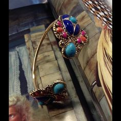 Bohemian Cuff-Host Pick This beautiful cuff features turquoise, blue, orange and pink faux stones set on a sturdy gold adjustable cuff. Measures 7.5 inches. (This closet does not trade or use PayPal) Jewelry Bracelets