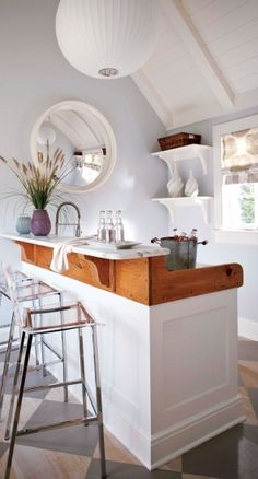 Love the bar how it splits painted and natural finish, very nautical--perfect for a pool house! Love the repeat of the round mirror and round paper pendant light...