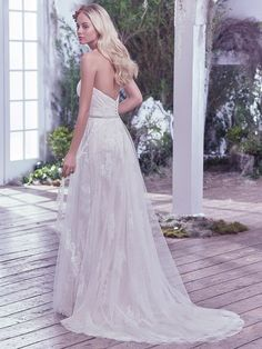 Maggie Sottero - BAILEY, Understated elegance is found in this romantic sheath wedding dress featuring layers of tulle, adorned with Swarovski crystals, pearls, and lace appliqués. A glimmering beaded belt and sweetheart neckline, add touches of refined femininity. Finished with covered buttons over zipper closure.