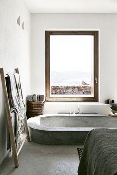 Stone bathtub in industrial bathroom with big window