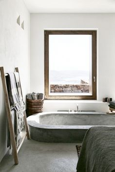 Love the semi-sunken stone/concrete bathtub in a rustic simple bathroom wonder what you see out of the feature window?