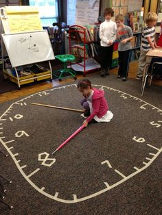 Creating a large clock on the carpet for students to interact with. A fun and engaging way to teach time telling! (Picture only)