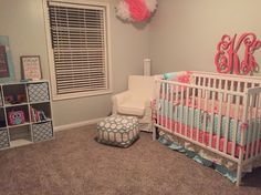 Coral, aqua and white nursery for baby girl.   White crib from Walmart. Peanut shell Gia floral / mila bedding collection from Amazon. Gia version also sold by Buy Buy Baby or Mila collection sold by Babies R Us.   IKEA jennylund chair in white.  Ottoman from Meijer.   White cube organizer by Target. Quatrefoil baskets from  Meijer.