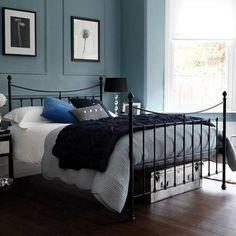 bedroom colours. blue paint, black metal bed frame, grey bedspread