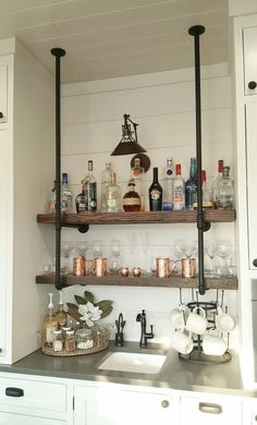Wet bar with industrial pipe and reclaimed wood shelving