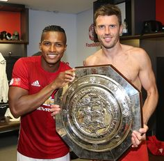 Antonio Valencia and Michael Carrick of Manchester United pose with the Community Shield trophy in the dressing room after the FA Community Shield...