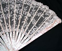 Circa 1860-80's, a elegant Brussels lace fan w/ Mother-of-Pearl sticks, with a design that is quite ornate. Trailing bobbin lace vines, flowers, and leaves in the design are further enhanced by the gentle scattering of Point De Paris throughout the fan.