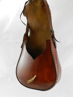 This bag is made of 7/8 oz. re-tanned yellow latigo and features a flap of the natural edge of the hide. This portion of the hide is the leg and its unique characteristics occur naturally in the tanning process. The front panel features an antler tip for the lace tie-down closure and the back features a crude looking stitched repair and patch for aesthetics and interest. The cut-out in the front panel provides easy access to this spacious bag. This bag is uniquely a one-of-a-kind bag and has…