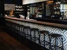 At this popular Spanish tavern on Main Street, brushed grey walls, geometric tile, and gleaming wood-topped stools provide a stylish backdrop for the chalkboard menu of pintxos (small bites popular in Northern Spain). Wood Bar Top, Wood Bar Table, Wood Bar Stools, Spanish Tavern, Wood Bar Cabinet, Cabinet Ideas, Outdoor Wood Bar, Bar Tile, Tapas Bar
