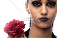 close-up of a indian female fashion model holding a rose. - Close-up portrait of a indian female fashion model holding a rose against white background, Model: Kiran Bahugun