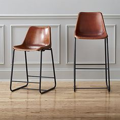 roadhouse leather bar stools :: Handmade leather composite with natural hide tones and markings saddles a contoured seat edged with a handsewn whipstitch and brass-painted rivets.