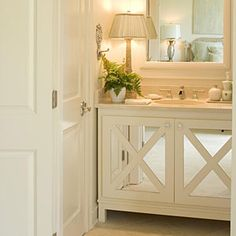 Comfortable Guest Baths | Make the Space Seem Larger | A cabinet vanity could overwhelm this tiny room, but matching the cabinet color to the wall color and mirrored cabinet doors help the room feel more open. | SouthernLiving.com