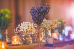 lavender & baby's breath in assorted jars as rustic wedding centerpieces