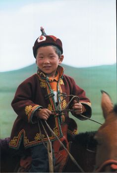 Mongolian Boy on a horse. These kids often know how to ride a horse before they can walk.