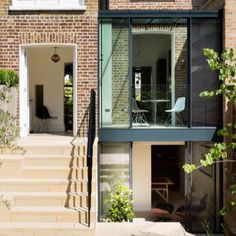 Double height glass extension using IQ's sliding glass doors and frameless balustrades. Grade II* listed home