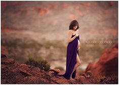 Lisa Holloway of LJHolloway Photography photographs gorgeous pregnant woman in the Valley of Fire on the red rocks wearing wind blown purple dress