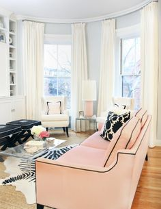 Rounded bay windows. Curtains a foot above the window trim all the way up to the moulding. curved rods. Love peach couch with black piping and Peekaboo Coffee Table