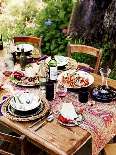 Outdoor wood, wood chairs, printed table runner, and printed dishes perfect for entertaining