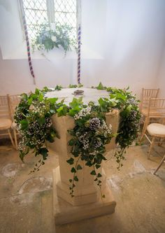Church font and window decorated with silvery pine cones and gypsophila for a lovely wintry feel. www.thelilylocket.co.uk