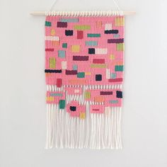 The Sprinkles Collection is a series of tapestry art, that displays sprinkle like shapes in various colours, on a plain coloured background. Each piece has been hand woven with a selection of cotton and wool yarns and hung on a raw wooden dowel. These wall hangings measure 39cm (15