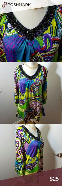 Multiples Gem Collared Psychadelica Paisley Blouse Excellent Used Condition. There is nothing simple or subdued about this blouse! From the black gemstone studded collar to the psychadelic colors reminiscent of the 60's. The sizing seems larger than listed, but measurements are in the picture. Multiples Tops Blouses