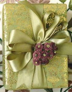 Decadent paper, a silky wide ribbon and a small flower cluster is the picture of holiday elegance ala Carolyn Roehm