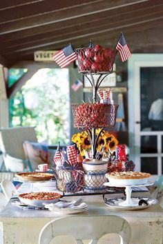 Put your pies on a pedestal for a dessert buffet on the porch — shown here, cake stands in vintage milk glass and clear glass. Blue-and-white transferware plates are the perfect backdrop for golden hand-crimped crusts. Build a festive centerpiece using tiered wire baskets. Fill with help-yourself treats like ripe fruit — as well as utensils. Rolled red, white, and blue bandannas can serve as napkins.