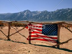 american flag on fence. - View of American flag on fence with mountains in background.