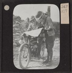 A motorcycle despatch rider and a colleague consult a map while wearing their gas masks, 1917.