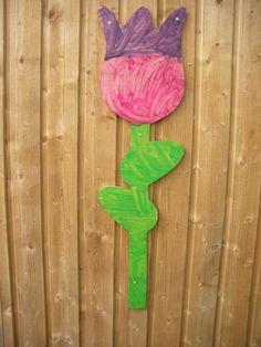 Vi har savet blomster ud i krydsfiner og børnene har malet dem. De hænger som udsmykning på Ude-SFOén,