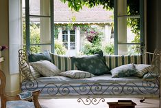 Iron detailing on the daybed, sicking stripes on the pillows and French doors opening onto the garden.