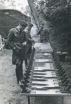 P.08 Luger pistols, spare magazines, and bayonets are prepared by an armorer for issuance to Luftwaffe troops in the field. Because it was the official (though not only) supplier of Luftwaffe Lugers, it is possible that these are factory-new wartime military Krieghoff pistols. The reviewing officer is an Oberleutnant.
