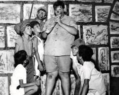 """QUARTELZINHO DO PÉ COM PANO foi o primeiro programa humorístico TV Gazeta. Começou em outubro de 1970. Era escrito, produzido, dirigido e interpretado pelo comediante Mário Alimari, conhecido pela essa sua criação, o Pé com Pano. O personagem surgiu na Excelsior, mas também esteve na Tupi e na Band, então Bandeirantes. Era uma ousadia brincar de quartel em pleno regime militar. Na imagem, Alimari está atrás, ao lado do """"meninão""""."""