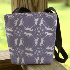 This classy and stylish equestrian tote bag features a faded vintage inspired blue color with a fun pattern of trotting horses or ponies with english horse bits and horse show ribbon rosettes all over.