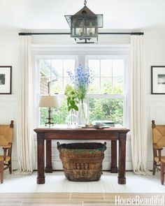 In the entry of a Shingle Style cottage in East Hampton, New York, decorated by Robert Stilin, an antique French basket provides storage for dog toys and leashes.