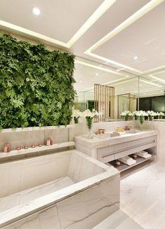 Detalhe do painel verde e banheira nesse banheiro todo de mármore