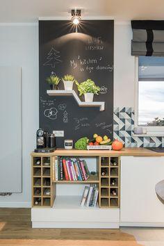 Skandynawska aranżacja kuchni, którą urozmaicono fragmentem ściany pomalowanym farbą tablicową. Drewniane blaty i półki...