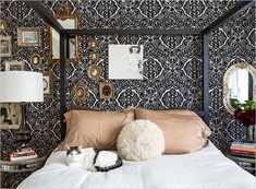 whimsical bedroom with black & white damask wallpaper & a collection of gilt framed treasures
