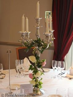 Wedding flowers - tall chrome candelabra table centre decorated with ivy and roses - by Floral Accents