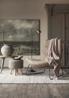 a chic reading nook with a leather chair, a floor lamp, a crochet stool