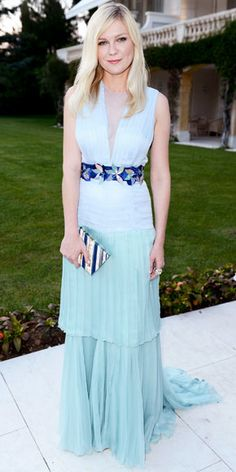 Kirsten Dunst posed for photos at the amfAR gala in a blue silk Louis Vuitton gown with a jeweled belt.