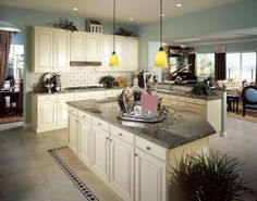 white-raised-panel-kitchen-cabinets-wtih-dark-granite-countertops_yellow-shade-pendant-lights_kitchen-island_recessed-lights_stone-tile-floor.jpg 1,024×806 pixels