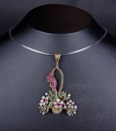 Edwardian yellow gold diamond, ruby and emerald flower pendant, tests 18 ct. Designed as a gold filigree weaved basket overflowing with old cut diamond, circular cut ruby and square cut emerald set flowers and foliage, the gold link basket handle tied with a circular cut ruby set ribbon. Measures 66 mm long x 44 mm wide. Weight 11.8 grams.