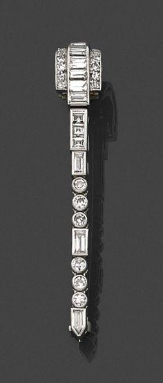 BOUCHERON  <br>BROCHE-BARRETTE ART DECO <br>en platine, en enroulement de diamants de différentes tailles, calibrés ou sertis clos, épaulés de petits diamants ronds. <br>Signée. <br>Vers 1925. <br>Longueur : 4,5 cm environ. <br>Poids : 5,4 g. <br>An Art Deco diamond and platinum brooch by Boucheron, circa 1925.