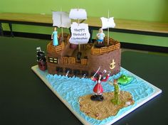 """This is a good top contender... Pirate Ship - This pirate ship, for my grandson's 5th birthday, is the first I have ever attempted  I used two 9 x 13"""" cakes and part of a 9"""" square cake.  My grandson specifically asked for the cake to be half chocolate and half yellow cake. The ship is covered in chocolate buttercream with fondant accents. I used square butter pretzels for the railing and piped the captain's wheel out of candy melts."""