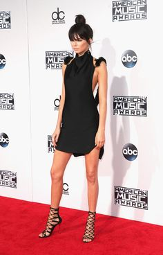 Kenall Jenner looked model-esque in a black minidress with a plunging back, topknot, and caged heels.