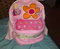 Pink bassinet made with diapers, onesies, burp cloth, and a bib