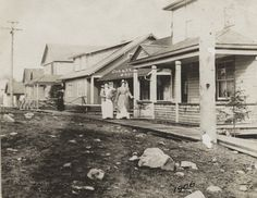 A photograph of Nurse Annie Saunders and another woman walking down a wooden sidewalk on Argentite street in Cobalt. View Image, Nurses, Small Towns, Cobalt, Ontario, Annie, Sidewalk, Photograph, Walking