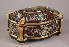 A Tahan casket A NAPOLEON III ORMOLU-MOUNTED MARQUETRY CASKET, SIGNED BY TAHAN, CIRCA 1850. Inlaid burl, copper, tin, ebony and ebonized wood and gilt bronze ornamentation, oval shape, decorated with scrolls and foliage, the domed lid decorated with a monogram in the center, the mounts highlighted by fluted pilasters, the lock engraved Tahan EBENISTE OF S. M. EMPEROR PARIS. #antique #vintage #box