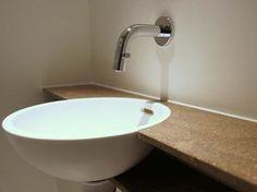 Eyecatcher in de toiletruimte is deze bijzondere waskom van Corian met kraan uit de muur - foto: Erbi